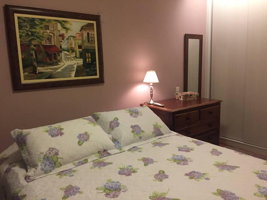 Suíte: cama queen e armário planejado no fundo.