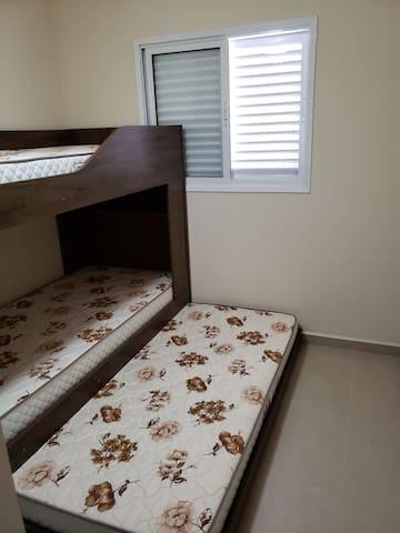 Quarto com beliche e cama adicional.