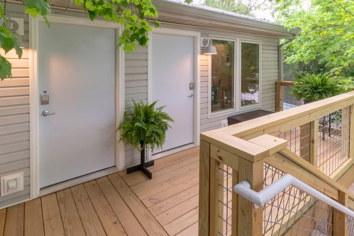 The outside of the apartment is a well-lit second story deck/porch.