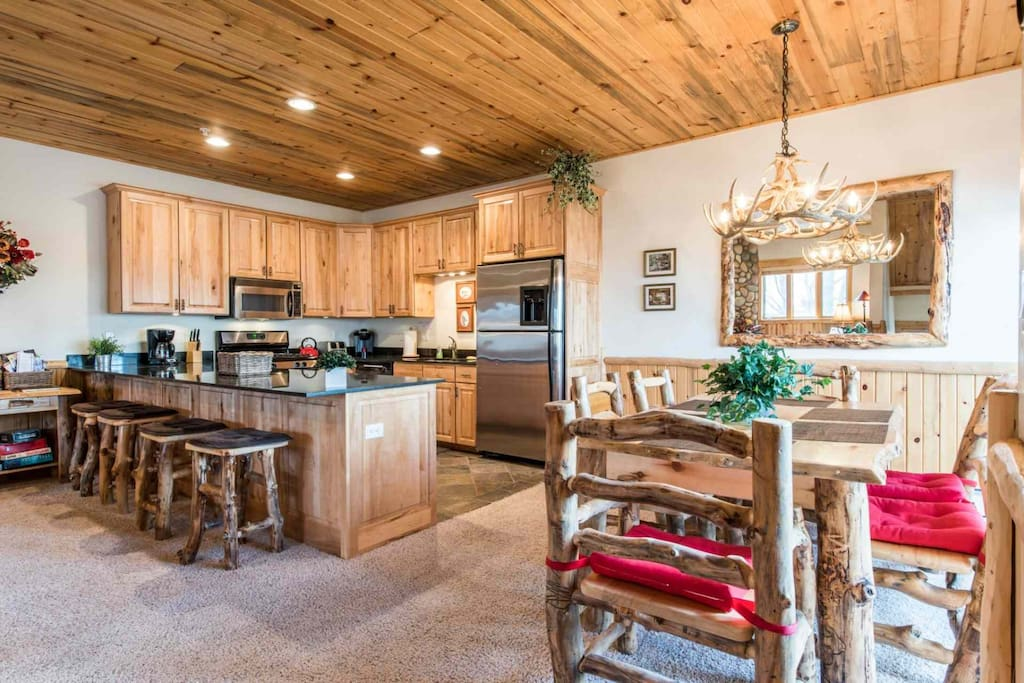 The formal dining room is decorated with an antler chandelier, custom log furniture and hardwood dining room table with seating for six (6).