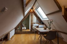 attic with dining table and kitchenette