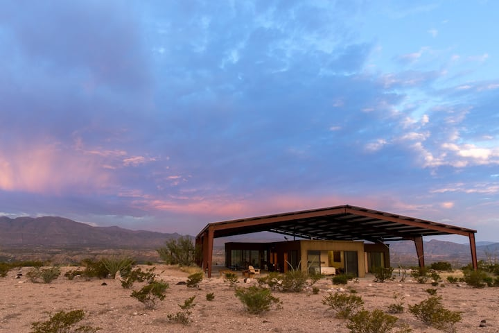Modern Solar Home, a modest and simple structure in a desert landscape under pink and blue sky.