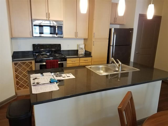 Fully equipped kitchen including coffee maker, toaster, dishware, flatware, pots and pans.