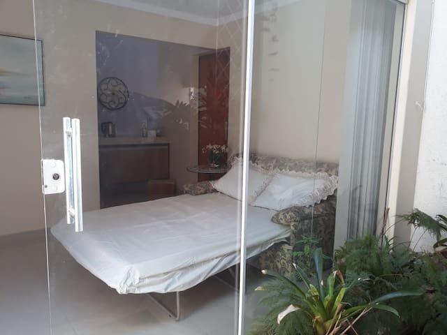 Sofá cama aberto com a demonstração das cortinas que podem ser abertas para trazer mais claridade ao ambiente. Espaço externo contém um pequeno tanque com carpas e plantas ornamentais