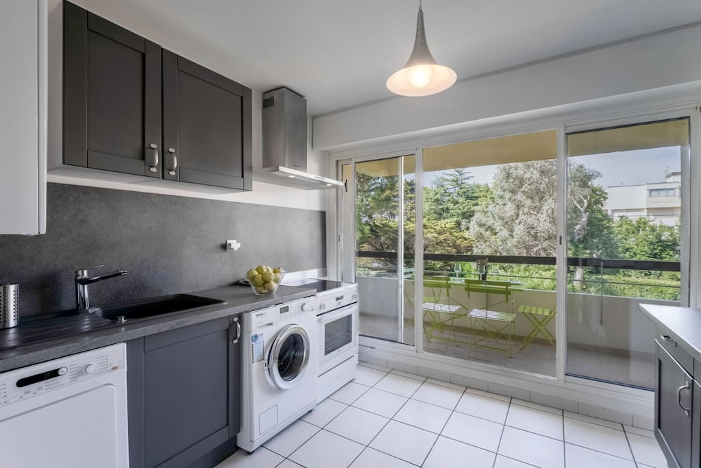 Kitchen open to a balcony with dining table. Cuisine ouverte sur balcon et une table repas.