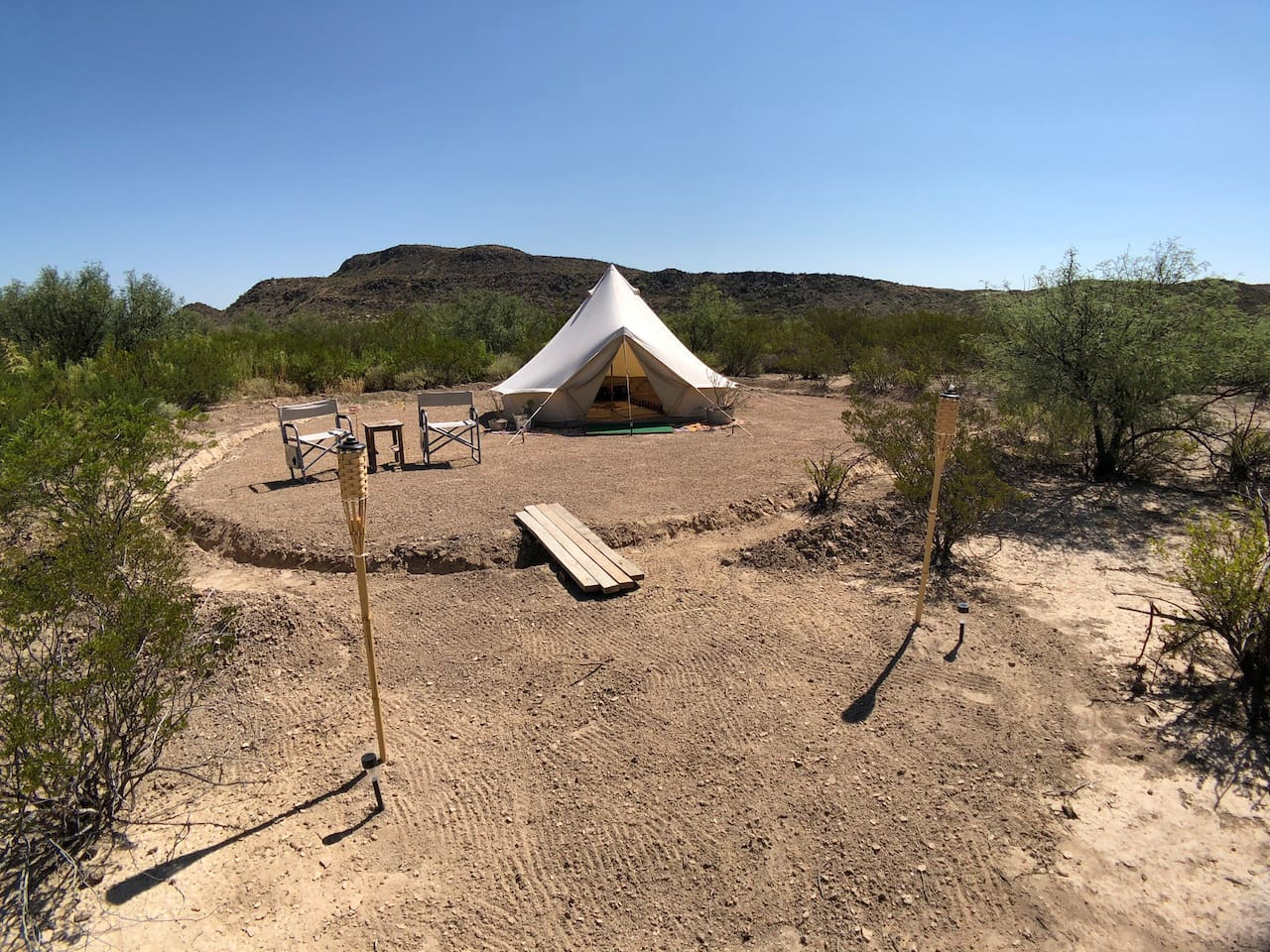 "The Mesquite Manor is a secure, water-tight bell tent nestled up under a ridge in the front portion of the ""Big Bend Glamping"" property. It has two twin mattresses and is surprisingly spacious inside. It could fit an extra person or two inside if you're traveling with kids."