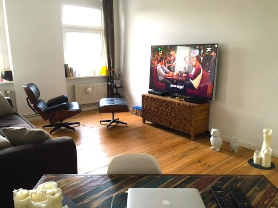 Livingroom with big sofa, lounge chair und diner- & worktable. 65 Zoll Sony LED TV with cable HD TV and BluRay Player.