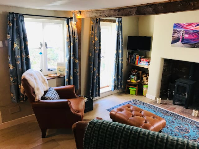 A cosy living room with underfloor heating and a log burner - views out over the small courtyard garden.
