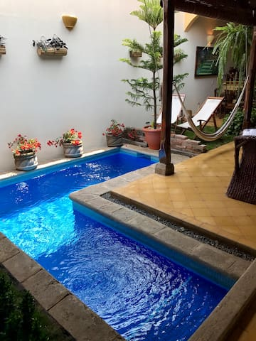 Pool has one seat / step on far right, then gradually increases in depth from 3 feet to 5 feet. Garden area with real grass has 2 hammock chairs and one hanging hammock for a relaxing afternoon or an evening in paradise!