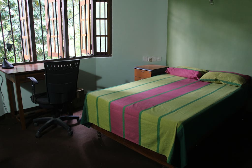 Bedroom - Mosquito net, writing table and racks are provided.