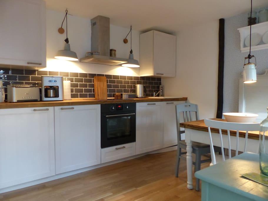Die Küche ist ausgestattet mit Waschmaschine, Geschirrspülmaschine, Herd, Ofen und einem gemütlichen Platz zum Essen