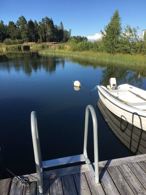 Båt med åror att låna ligger förtöjd vid tomtens brygga