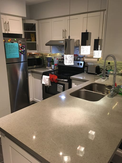 state of the art kitchen with brand new stainless steel appliances (stove+microwave+dishwasher+refrigerator+toaster+coffee maker) and kitchen utencils, cutlery and ample storage space