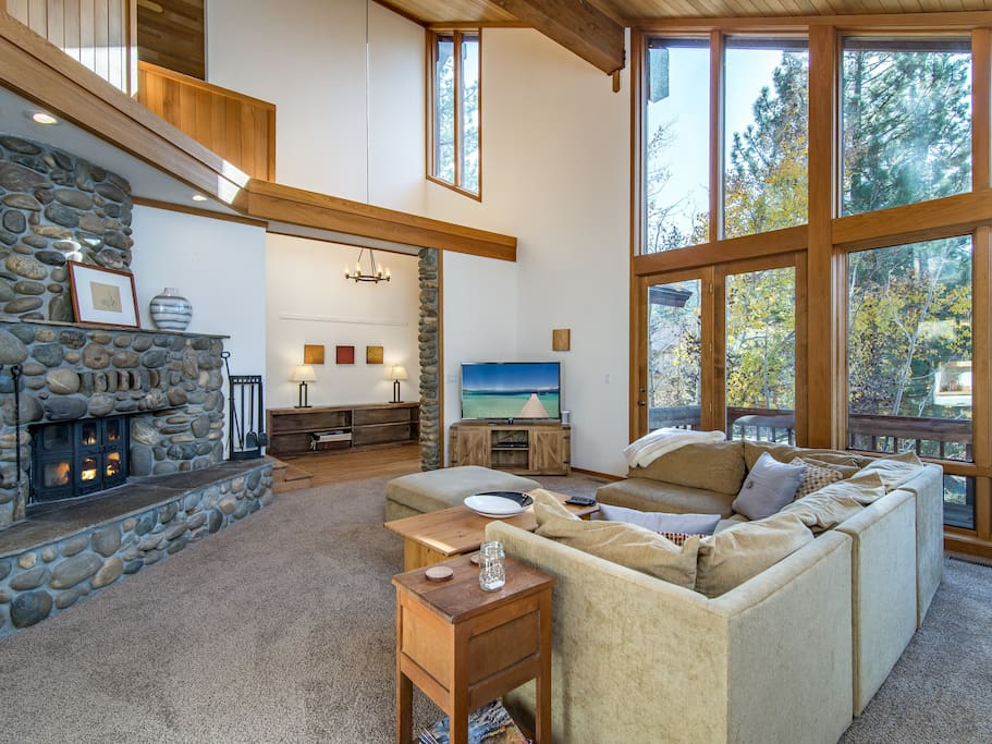 Expansive windows and vaulted ceilings create a welcoming space. A great place to relax and enjoy the view of the surrounding forest.