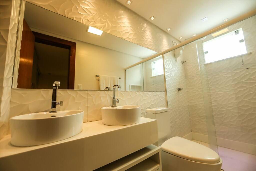 Banheiro da suíte com ducha e Led azul  (cromoterapia), armário com duas pias e torneiras inoxidável,  blindex, espelho e sanitário.