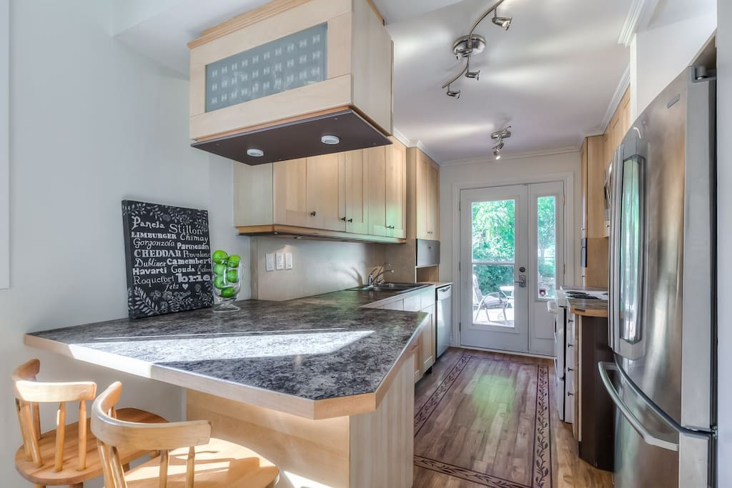 Large fully equipped kitchen with walk-out to large deck overlooking magnificent backyard.