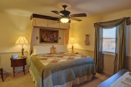 This room has is divided by a wall and doorway the main part has a king size bed and the seating room has 2 twins.