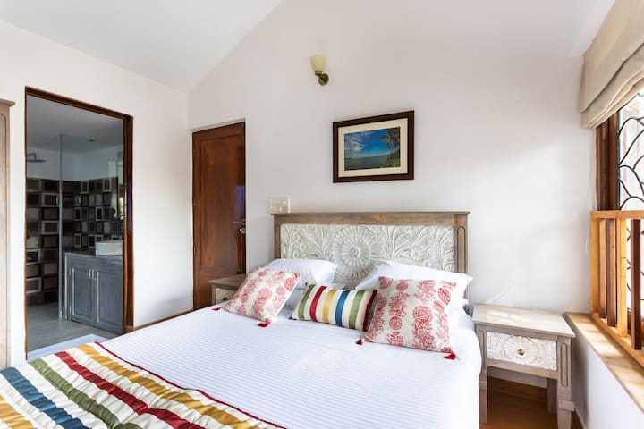 The Third Bedroom is located on the First floor with a cupboard, Airconditioner, and En-suite bathroom  - showing the entrance to the bathroom to the left and view to the right. The Door Behind the bed is the entrance to the Room.