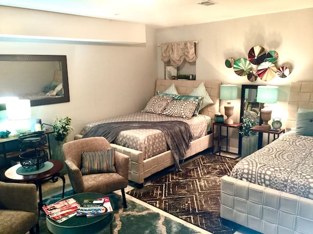 Cozy suite is perfect for 2-4 guests. Features 2 queen beds, sitting area, bar, 55-inch 4K TV, and dresser.