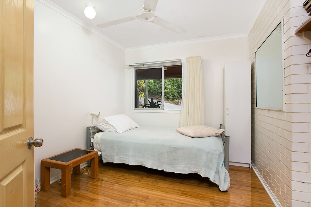 Spacious private room featuring a comfortable King Single bed, wardrobe and desk.