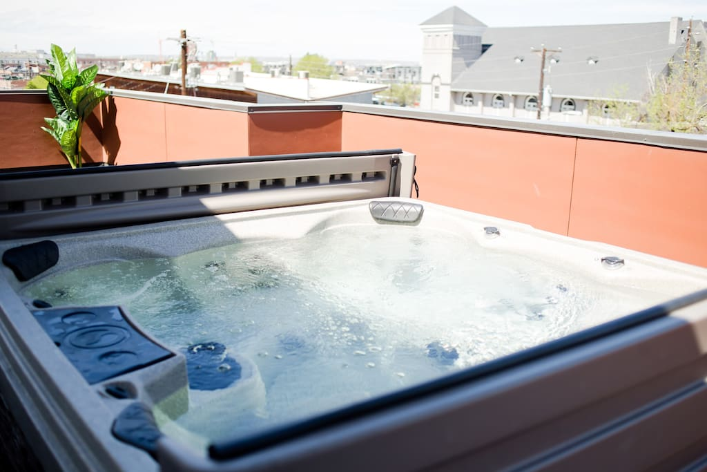 Beautiful upstairs deck with views of the city, heated 6-person tub, towels, BBQ and sitting area!
