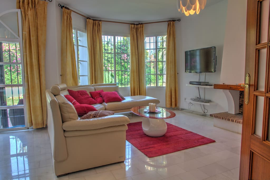 Bright and ample living room, with fireplace, leather sofa, music system and flat screen TV