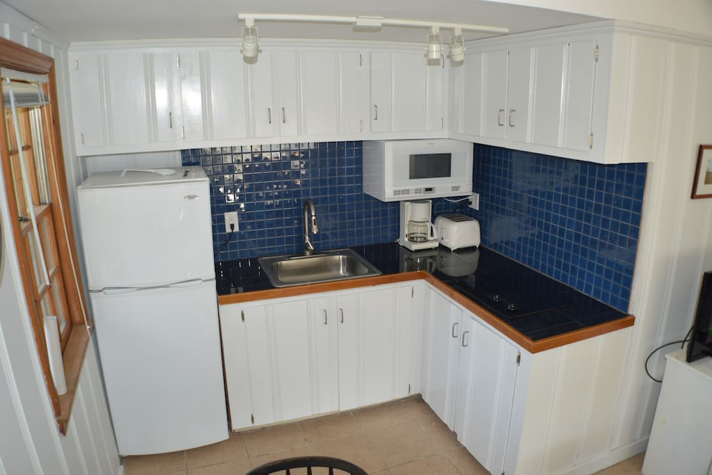 Newly refurbished kitchen is fully furnished and includes granite counters and tile backsplash and cooking supplies