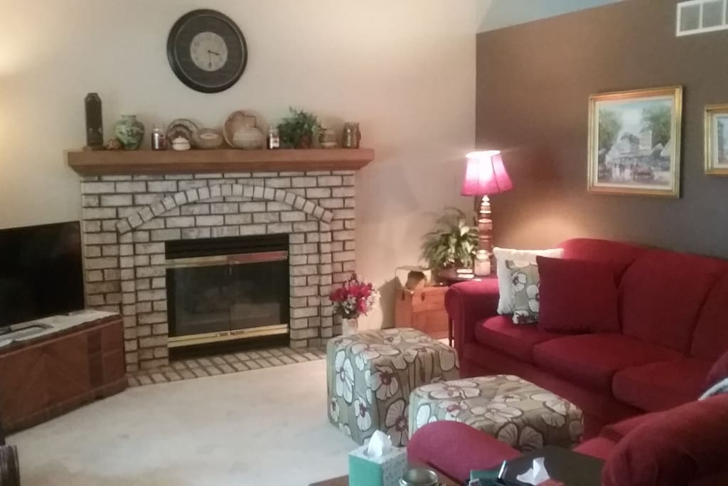 Open concept living area with sectional, gas fireplace and flat-screen.