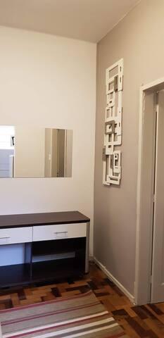 Sala com sofá, estante e espelho.