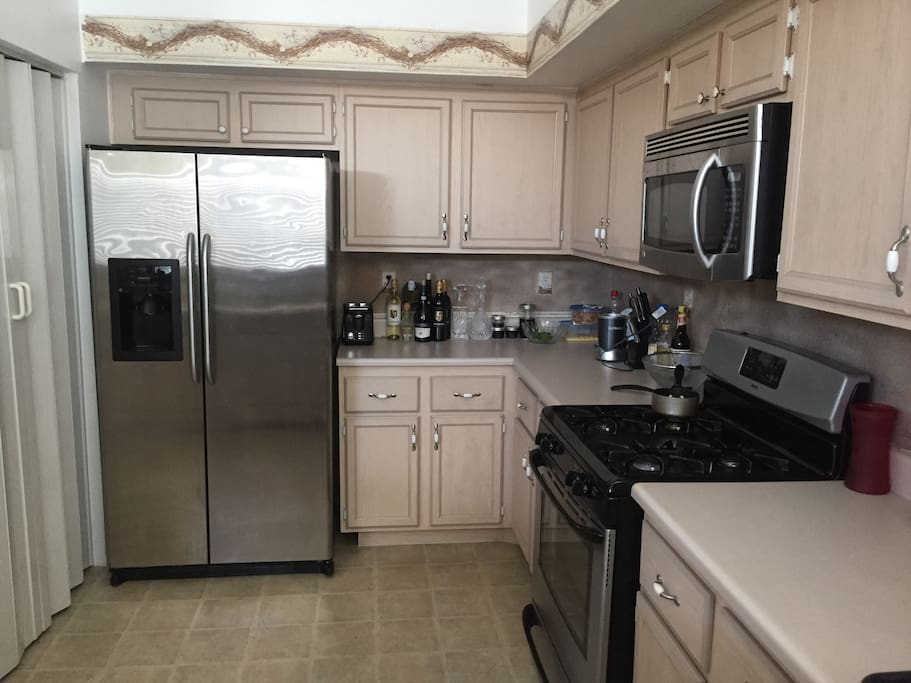 Open space equipped with stainless steel appliances, coffee maker, nutrition bullet drink blender