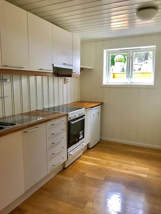 Lyst og innholdsrikt kjøkken med kjøleskap, komfyr, mikroovn og vaskemaskin