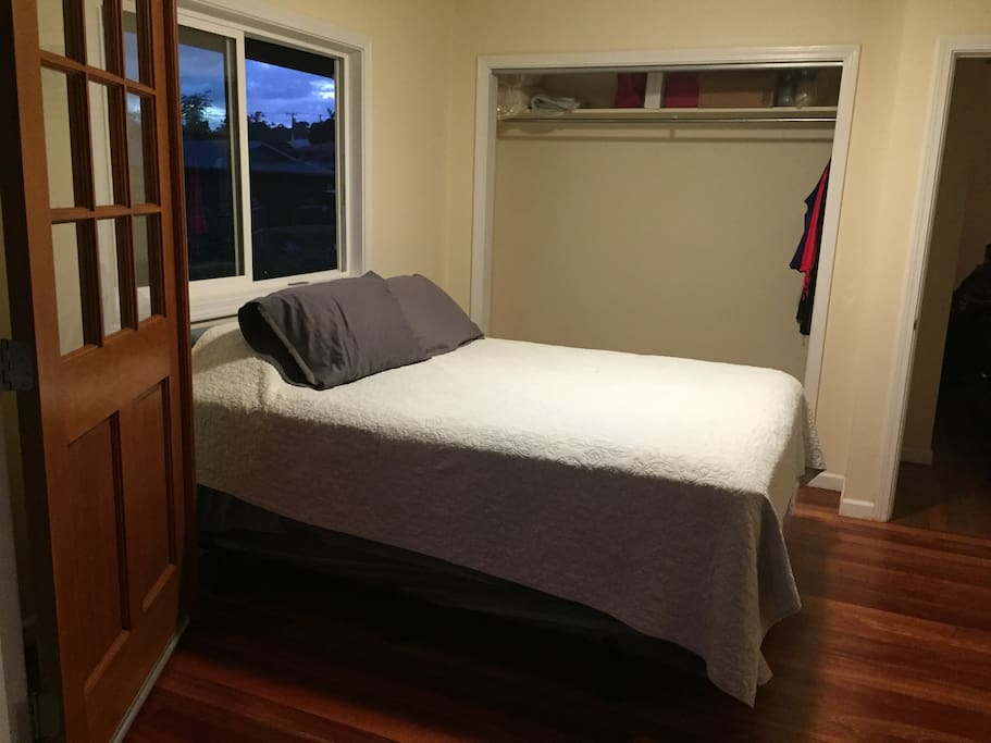 This is the room with a queen bed, closet space, and local hardwood flooring.
