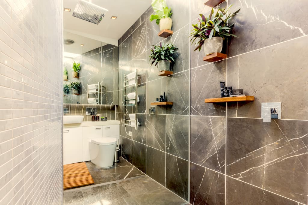 Ensuite Bathroom - clean & modern with large shower rain head.  This bathroom is light filled from the skylight above, the walls are mirrored & grey Marble.