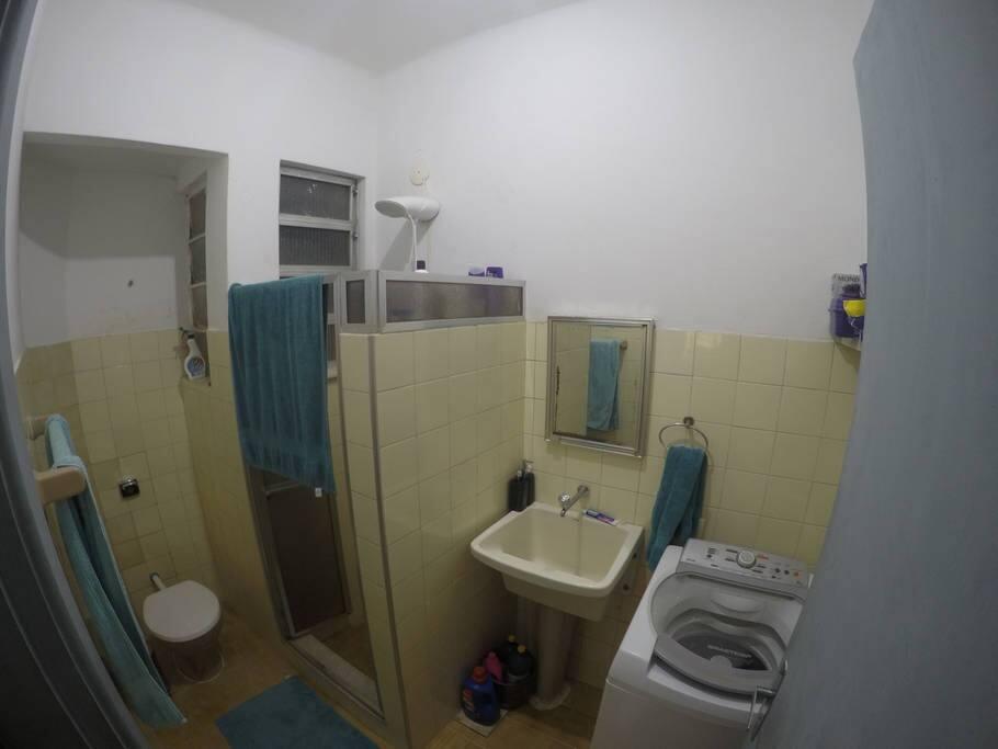 Banheiro com Máquina de lavar e chuveiro elétrico