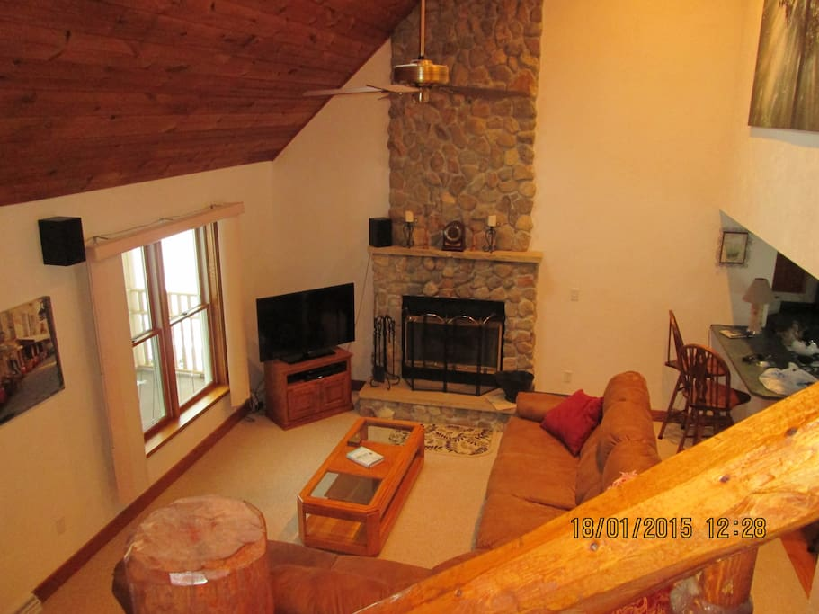 wood burning river rock fireplace with knotty pine cathedral ceilings