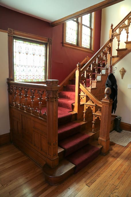 Beautiful main staircase, hand carved railings and stained glass.