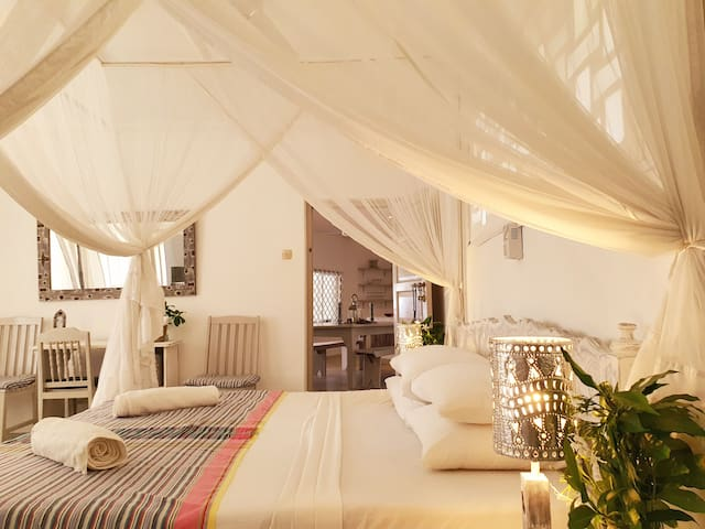 King size bed with mosquito nets and fan overlooking turtle bay beach