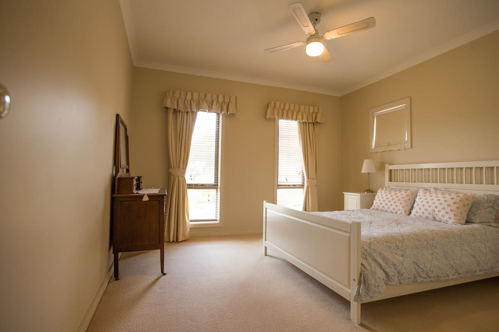 3rd bedroom with queen bed, ceiling fan and built ins