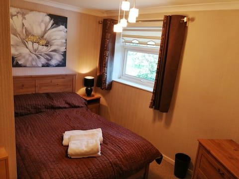 Cozy bedroom with king size bed, fitted wardrobe and chest of drawers.