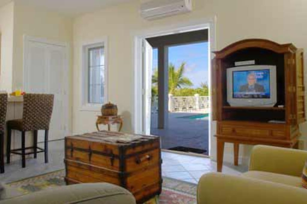 Small open concept living room and furnished kitchen with a flat-screen and DVD player (no cable TV-bring your own content and connect with the provided HDMI cable). The french doors open to the pool deck.