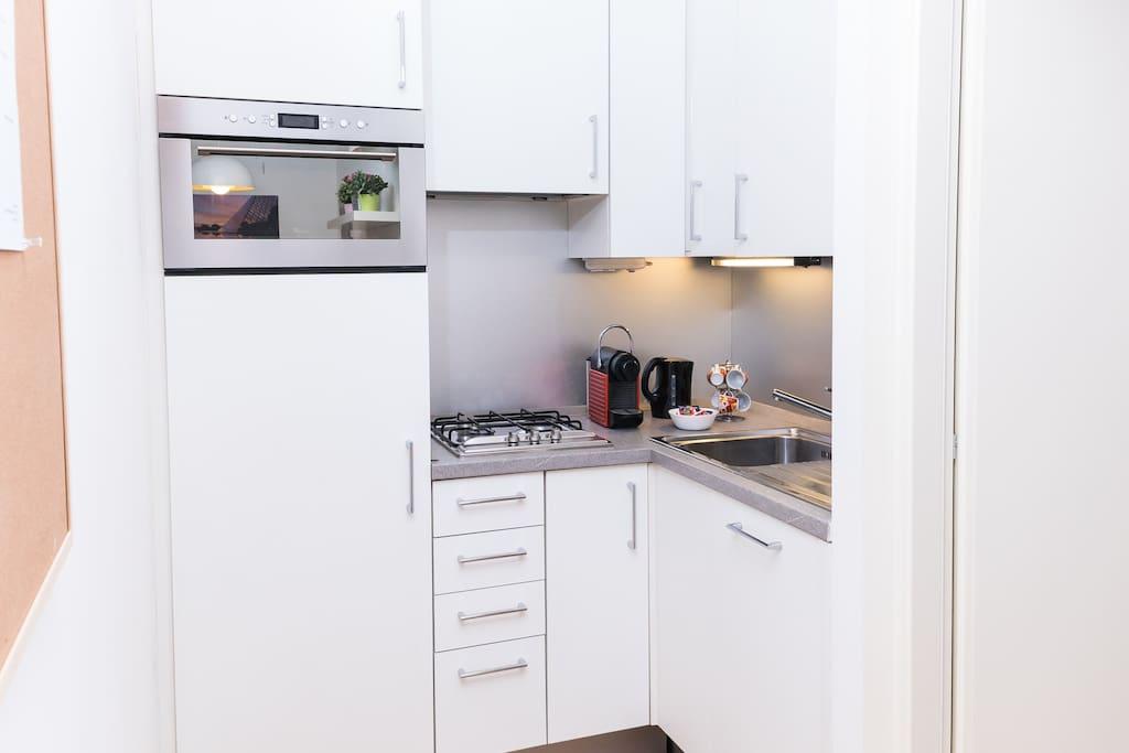 Cucina con macchina per caffè Nespresso, bollitore, forno a microonde, frigorifero, lavastoviglie, freezer e stoviglie per cucinare e pranzare