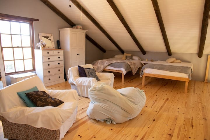 Upstairs  Attic room has two double beds with an open areal view on kitchen and lounge area.