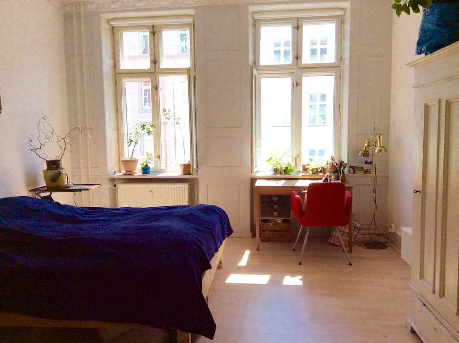 The private room with a desk, and the bed. Lots of plants and big windows towards Vesterbrogade. Morning sun can be kept out with my new curtains.