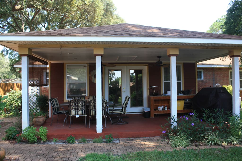 Covered back porch with Dinning table and six padded chairs and a large natural gas grill.