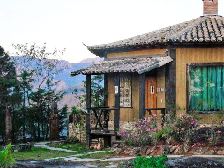 Chalé em estrutura octogonal, com lareira,sala, cozinha e decoração colonial