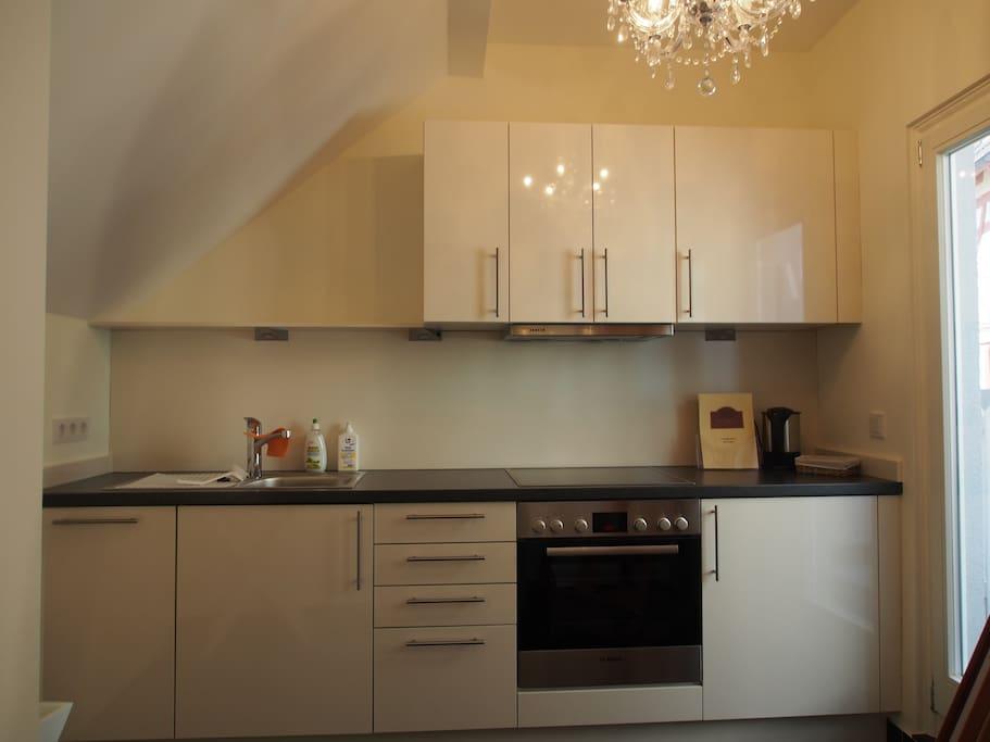 Hochwertige Küche mit Spülmaschine und Kühlschrank, sowie mit Geschirr und Besteck