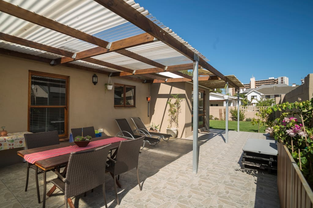 Sunny semi-covered patio with braai area leading into garden