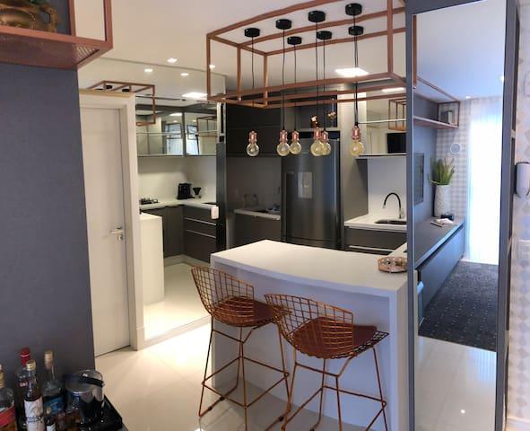 Cozinha com forno elétrico, geladeira e cafeteira de expresso