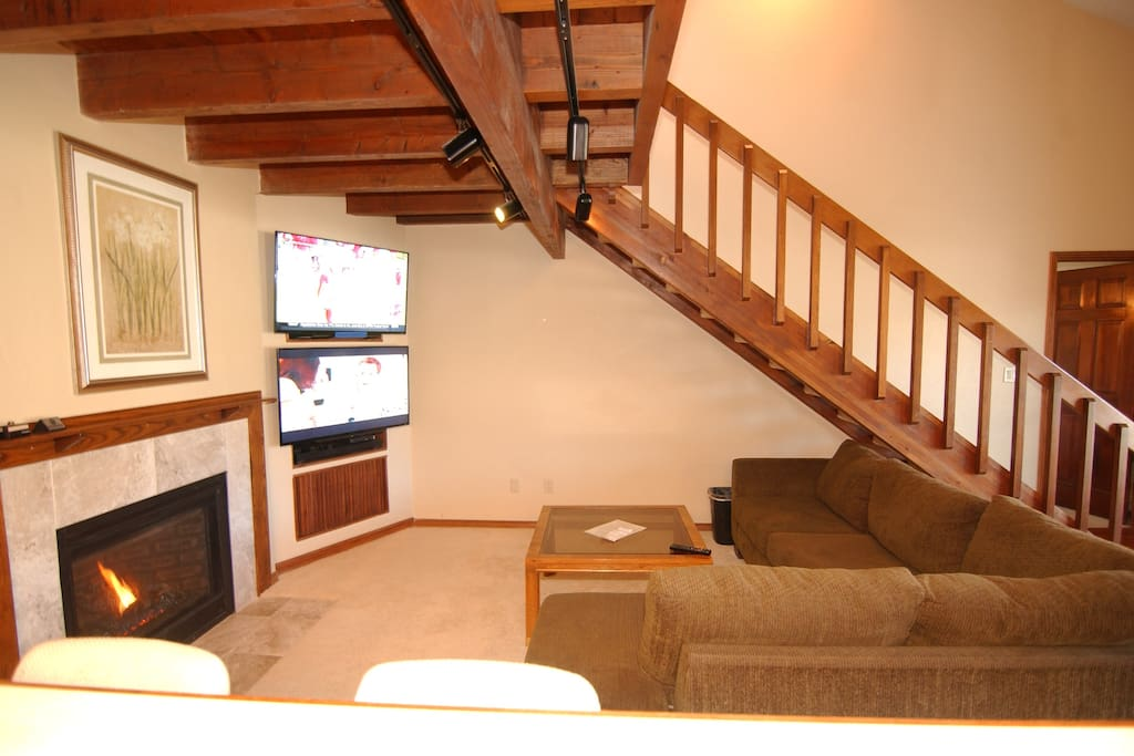 Living room with natural gas fireplace, large couch & Dual TV entertainment wall.