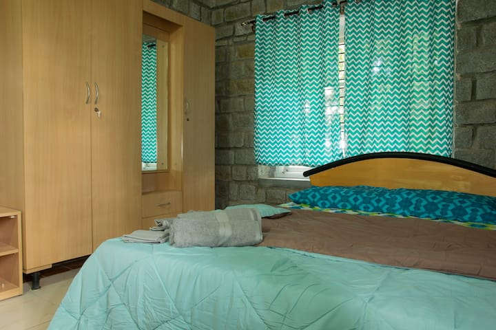 A cozy well furnished bedroom with a queen sized bed and attached bath on the first floor